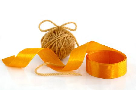 Ball with yarn and ribbon against the white background