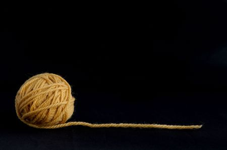 Yellow ball with yarn against the black background