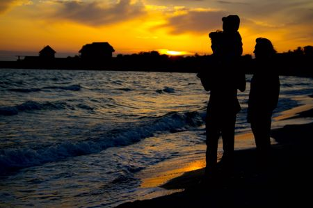Silhouette of the young family on the shore of the black sea Stock Photo - 6567046