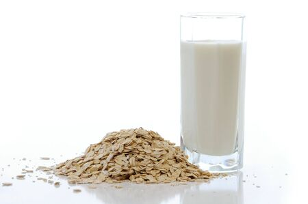 Oat flakes with the milk against the white background