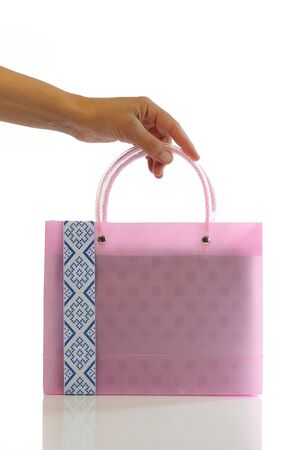 Female hand holds the small pink bag