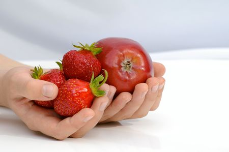 Child holds in the hands apple and strawberries Stock Photo - 7498524