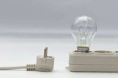 Electric lamp with extension plug-wire on light background
