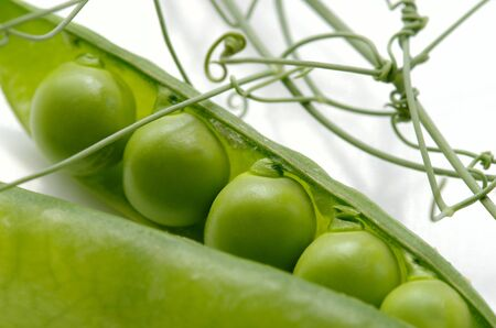 Green peas against the white background by the closeup Stock Photo