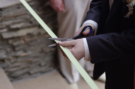 A man with scissors cutting the ribbon at the opening ceremony