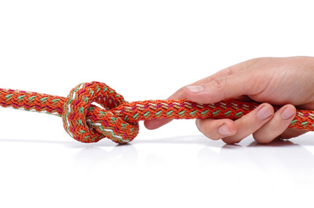The human hand is holding a rope tied in a knot