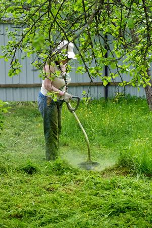 grandmother mows the grass