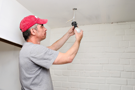worker changes the light bulb in the apartment