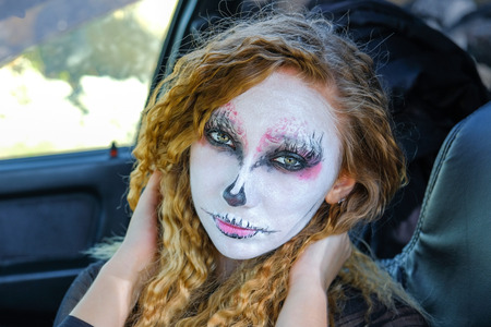 a zombie girl with black eyes and a bloody mouth in the car