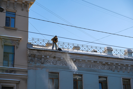 worker removes snow from the roof