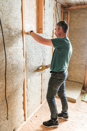 the worker insulates a country house of mineral wool