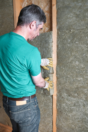 worker insulates a country house of mineral wool