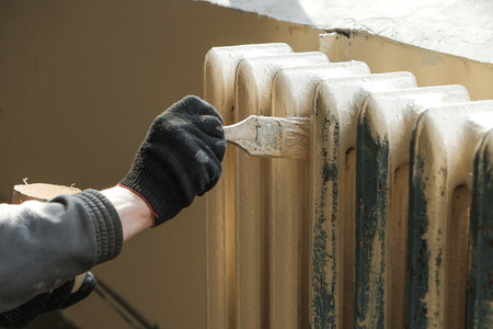 worker paints the metal water heating radiator Banco de Imagens