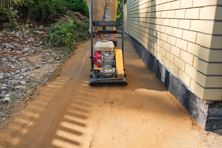 Builder ramming sand around the house at the construction site Stock Photo