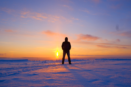 the silhouette of a man on the background of a winter landscape at sunset