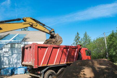 Bagger gräbt Lehmboden auf der Baustelle