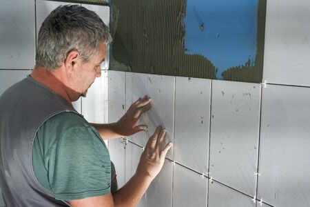 worker puts ceramic tiles on the construction site