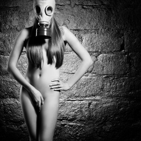 The naked beautiful young girl in a gas mask Stock Photo