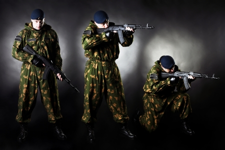 Armed man in uniform on black background studio photo set photo
