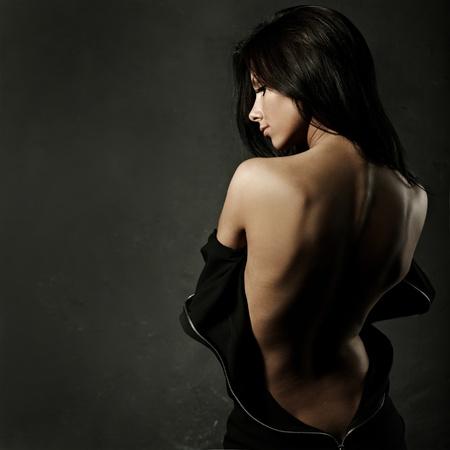 culo: mujer hermosa en vestido de noche sexy contra el fondo oscuro Foto de archivo