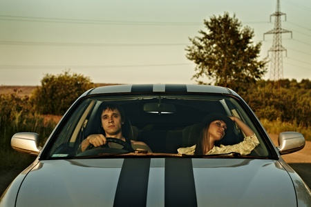 Young couple in the sport car on a country road Stock Photo - 17482956