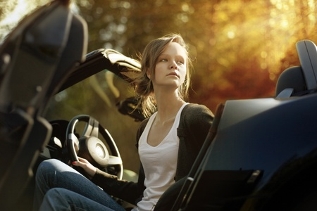 sexy beautiful young woman driving her convertible car photo