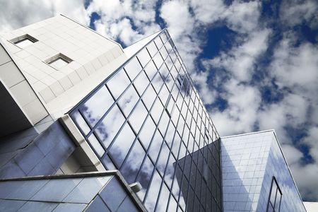 ventanas de los rascacielos con reflexiones sobre un fondo de cielo nublado Foto de archivo