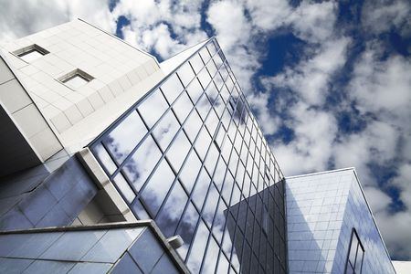 windows of skyscraper with reflections on a background cloudy sky Stock Photo