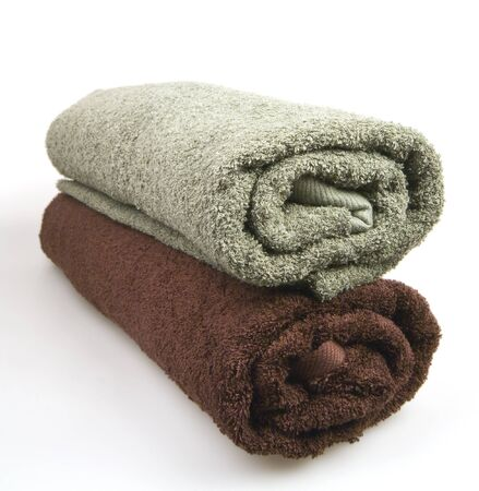 Two rolled fluffy towels on a white background