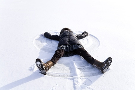 young woman kidding on snow in winter day