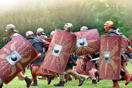 Gessate, Milan, Italy: April 07, 2019: reenactment of ancient Roman legionary soldiers during battle against Gallic army and life scene in war training camp with several dueling Foto de archivo - 128467346