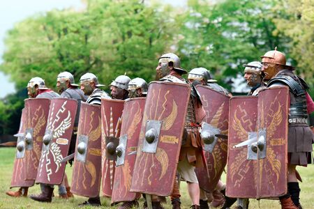 Gessate, Milan, Italy: April 07, 2019: reenactment of ancient Roman legionary soldiers during battle against Gallic army and life scene in war training camp with several dueling