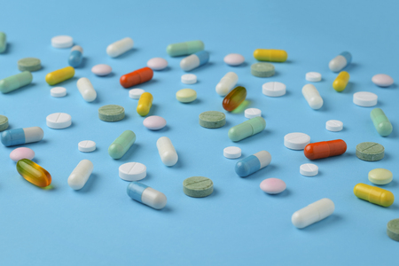 Unsorted pharmaceutical preparations on a blue background