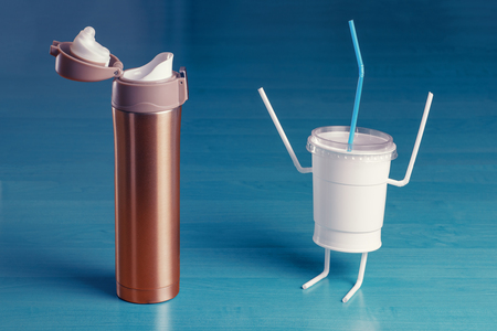 Disposable plastic cup with hands up in front of the flask. The concept of replacing disposable plastic. Stock Photo