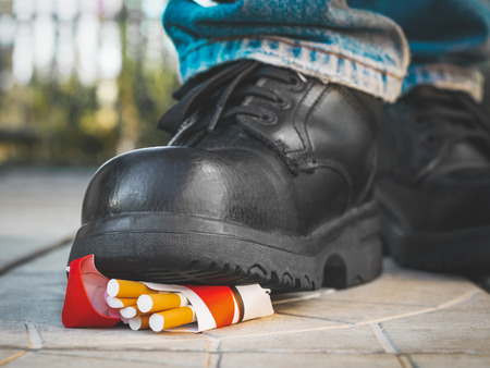 Foot in a black boot crushes a pack of cigarettes.
