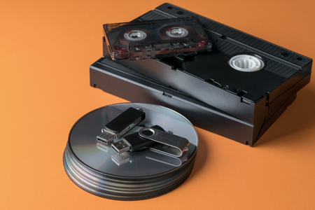 A stack of compact discs and video-audio tapes and a flash drive on an orange background. Stock Photo