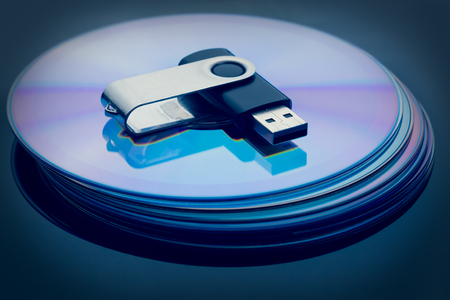 Flash drive on a stack of compact discs as a data storage concept. Stock Photo - 122172418