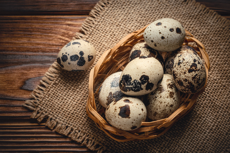 Top view quail eggs in a basket on jute fabric and wooden background.