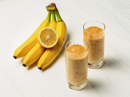 Banana smoothie in a glasses and a bunch of bananas with lemon.