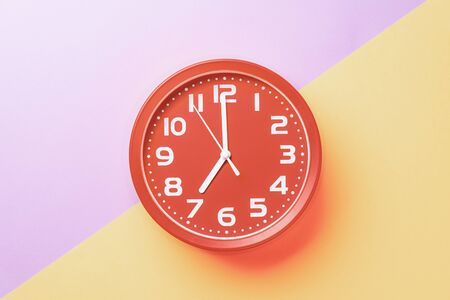 Red clock showing seven oclock with white numbers on a yellow lilac background. 版權商用圖片