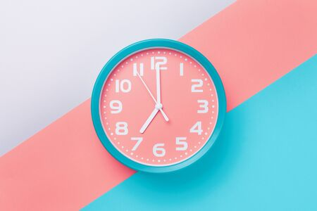 Alarm clock with a round dial on a colored background in the style of material design.