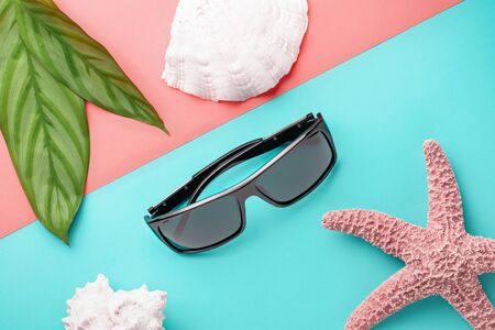 Sunglasses and seashells with starfish on a colored background as a summer holiday concept Фото со стока