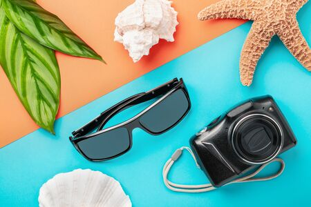 Sunglasses and digital camera on color background as a summer vacation concept