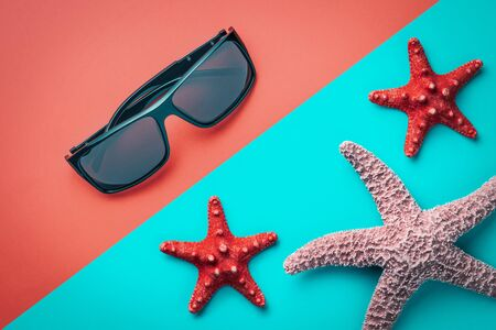 Flat lay sunglasses and starfishes on a colored background. Фото со стока