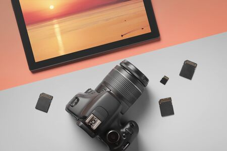 Top view modern digital camera and tablet with a photograph of the sea landscape on a gray-orange background. Stok Fotoğraf