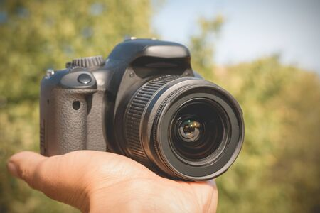 Modern digital camera held in the hand of a man.