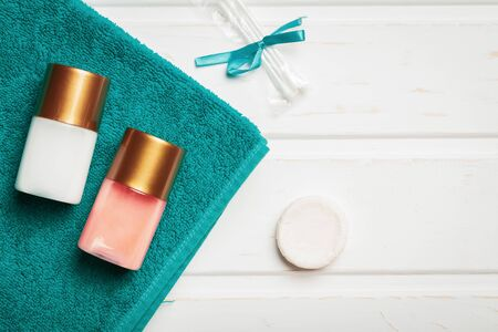 Bottles with shower gel and shampoo as well as soap with cotton buds and a towel as a concept of hotel service.