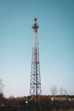 Cellular base station telecommunication tower located among residential buildings.