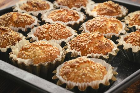 Baked cupcakes with sesame seeds in aluminum molds on a baking sheet.