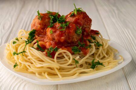 Nahaufnahme eines einsamen Tellers mit gekochten Spaghetti mit Frikadellen, gewürzt mit Petersilie, auf einem weißen Holztisch.